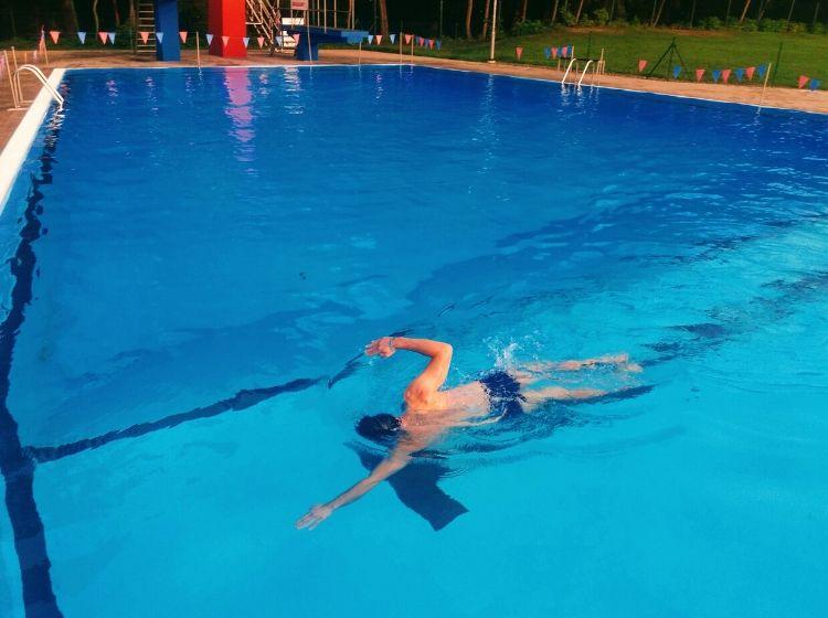 Marek plave na letním koupališti