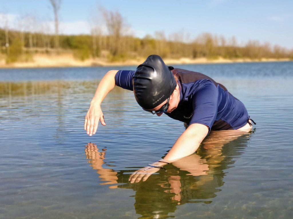 Alice stojí na mělčině a nacvičuje správný přenos paže a úhel zasunutí ruky do vody. Voda má 16 °C, je jaro a plavat už se dá